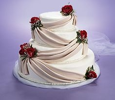 Fondant drapings create the lavish look of elegant silk fabric on this stacked tiered cake. Truly spectacular!