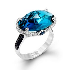 This grand 14K white and black gold ring, from our Refined Rebel Collection, is set with a beautiful 9.69ct Blue Topaz center stone surrounded by .32ctw of white diamonds and .61ctw sapphire.