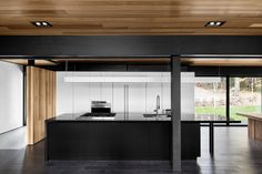 This 1940s lake house was given new life and an open-plan update thanks to architect Alain Carle. The kitchen's black countertops were cut from Nero Assoluto granite. The sink and faucet are from Quebec-based company Rubi. Appliances are from Wolf.