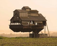 Floating house, Ukraine. This building is a part of a potato sorting station. The metal cone is used for loading potatoes into trucks. It's a common construction in agricultural regions of Ukraine, but this one looks like misplaced or partly dismantled.