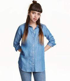 Denim blue. CONSCIOUS. Long-sleeved shirt in soft, washed Tencel® lyocell with a turn-down collar, chest pocket, and buttons at front and at cuffs. Rounded