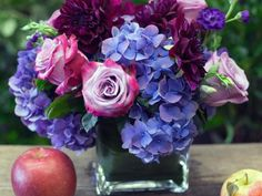 Blue hydrangeas, purple roses and vivid mums. Floral design by Hallie's Garden .