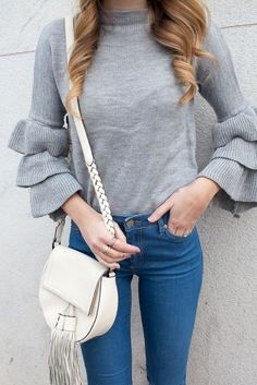 A ruffle sleeve sweater paired with distressed denim.
