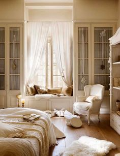 Window seat - glass fronted wardrobes with curtains and ribbons.  Warm hardwood floors