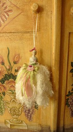 Soft, feminine decorative tassel for an extra special addition to your home decorating or as a gift for an extra special person. Tassels make a wonderful gift for the person who has everything! Her skirt is made of white fringe and is adorned with a handmade flower. Ive used pastel green, and pastel pink ribbons for the bow and tails that cascade down her dress. The hanger is made from a thin silk ribbon.    This tassel measures 9 in length from the top of her head to the bottom of her…