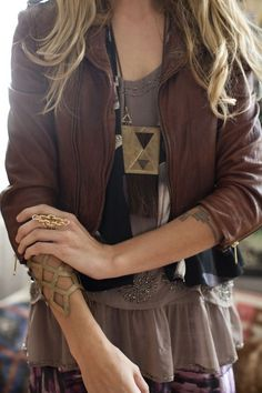 winter goes bohemian with this maxi dress layered underneath a vest and earthy leather jacket paired with chunky jewelry