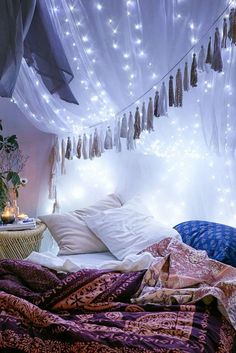 dreamy canopy lighting Create year-round festivity with clear string lights behind a drapey translucent canopy for lush Bohemian bedroom vibes.