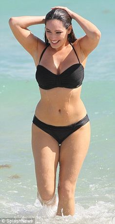 Stepping out: Kelly wades out of the surf during the latest day on her shoot in the Sunshi...