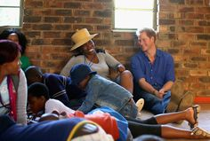 Prince Harry photographs in Lesotho during a visit to his charity Sentebale Prince Harry sits next to a volunteer who was laughing at his singing during a visit to a Mamohato Network Club for children living with HIV at St Paul Centre on December 9, 2014 in Maseru, Lesotho