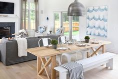 Open floor plan boasts a galvanized metal pendant illuminating a blond x based dining table lined with white Tolix Chairs one one end and a white farm bench on the other end.