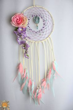 8 x 27 Dream catcher wrapped in a cream colored faux suede with light pink hemp, amethyst beads, amazonite beads, a druzy pendant with an aqua aura quartz point, peach and mint feathers, a peach rose, and lavender colored flowers.  Amethyst is known as a psychic protection stone that can help with protection from psychic attacks and negative energy during mediation. It brings calm, balance, patience and peace. You can use it to increase intuition as it balances your crown chakra and is used…