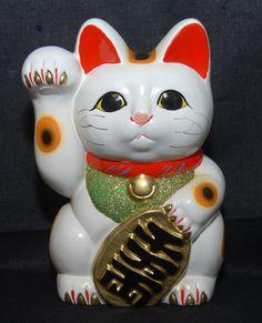 """Significa """"gato de la suerte"""". Este simpático gatito que usted encontrará en la entrada de todo negocio en Japón mueve su patita izquierda para atraer dinero, mientras que la pata derecha atrae visitas. Un Maneki Neko dorado significa prosperidad económica. Un Maneki Neko sirve para atraer el amor. Un Maneki Neko verde significa salud y seguridad"""