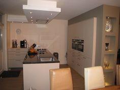 Moderne keuken met rechte greep, een granieten blad en hoge kast gedeeltelijk verdiep in bouwkudige nis. — bij Hendrik Ido Ambacht.