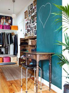 VEGGPLASS: I denne entreen er veggene tatt i bruk til b�de oppbevaring og tett i tett med familiebilder. De brune trehyllene gj�r det enkelt � f� oversikt over skoene, og de tar ikke opp gulvplass. Den gr�nne veggen er malt med tavlemaling.