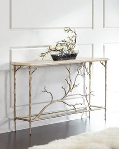 "Handcrafted console. Cast aluminum base; silver-leaf finish with golden and green highlights. Italian silver travertine top with honeycomb steel core to reduce weight and improve strength. 60""W x 14""D"