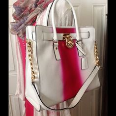 """MK HAMILTON SPRAY WH/FUSHIA N/S LEATHER TOTE Add a pop of color to your wardrobe with this graffiti-inspired design. Features leather exterior, golden hardware, top handles; 4-3/4"""" drop, chain & leather shoulder strap, frame top w/logo-engraved lock detail, hanging key, interior with MK signature in Khaki color, one zip pocket, three open pockets, & one cell pocket, protective feet on bottom. Dimensions: 14"""" W x 13"""" H x 6-1/4"""" D THIS IS A BRAND NEW BAG. COMES W/DUST BAG & CARE CARD. NOT A…"""