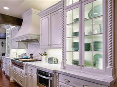 Glass cabinet doors are an excellent option for homeowners wishing to display their dinnerware. In this kitchen designed by David Stimmel, the glass-front cottage cabinets display beautiful mint green dinnerware, providing color in this otherwise white kitchen.