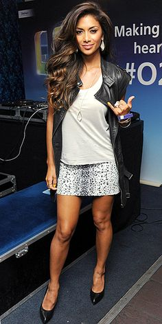 Nicole Scherzinger in animal print miniskirt and black leather vest with black patent leather heels.