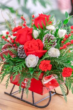 White spray roses, miniature red carnations, and white button spray chrysanthemums are accented with flat cedar, grevillea and huckleberry. Delivered in Teleflora's Vintage Sleigh. Sleigh bells ring! Sliding into the season in a vintage metal sleigh with rustic antique finish and pull rope, this lush mix of snow white roses and winter greens delivers classic Christmas style!