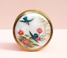 A vibrant Convertible Powder Compact made by Margaret Rose in the 1950s, in excellent condition.  The colourful hummingbird and water lily design sits on a faux mother of pearl style background; this image is covered with a clear plastic dome. Small sections of the painted design are pressed onto the slightly higher dome, giving a beautiful 3-D effect to the design. There are a couple of small dents to the raised plastic cover, but these do not affect the function or appearance of the piece…