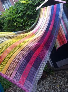 A large lightweight rectangular shawl with stripes of lace and stranded knitting in a patchwork of harmonizing natural colors.