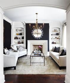 layout and dark walls with white built ins, fireplace, and furniture. Very clean and crisp space.