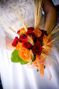 wedding flowers: red and orange roses with sprouts of wheat ideal for a fall / autumn wedding