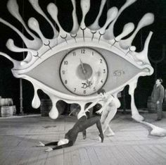 """""""04 Apr 1962, Brussels, Belgium: Some characteristic symbols of the unique art of Salvador Dali- eye, clock, crutches- dominate the stage of the Theatre Royale De la Monnaie in Brussels as Ludmilla Tcherina, famed ballerina, rehearses with an unidentified partner. The new ballet, with scenery by Dali, will feature the music of Scarlatti."""""""