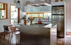 Na cozinha ampla e iluminada, o material dos armários e da ilha central é de aço inox. Projeto é assinado pelo arquiteto Jorge Siemsen
