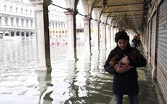 A man carries his dog while walking through the flooded St Mark's Square during a period of seasonal high water Travel News, Venice, Carnival, To Go, Aqua, Louvre, Seasons, City, Water