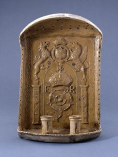 Candle bracket; earthenware; pale buff ware, yellow glazed; an oblong panel, having in relief the Tudor rose crowned and E R; above, the royal arms with supporters; a tray below has two sockets for candles, and above is a pierced canopy. Made in Hampshire or Surrey. From British Museum.