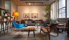 Conforto e elegância conduzem a decoração da sala. O destaque fica por conta da mesa de centro ETR, de Charles e Ray Eames, de design clássico, e as cadeiras de bar da Thonart, com jeito retrô  Foto: Divulgação