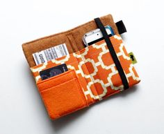 This original design from T-L-C Pouches is a multi-use cell phone case and wallet, designed and handmade here in my strawbale home-studio. Carry your cell phone, iPod or camera and your money, cards headphones all in one stylish and convenient place.  Mix together some modern design flair, add a little pumpkin spice coloring and you get this fiery little gem of a wallet! Both the outside and inside of this wallet features a pumpkin orange and modern chain design fabric. A felt, orange pocket…