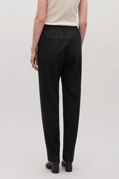 Model side image of Cos panelled trousers with elastic waist in black