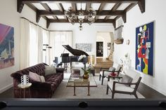 In this Spanish contemporary home, a Modo chandelier from Roll & Hill hangs in the living room, which also contains No. 27 chairs from Holly Hunt, a Cuadras coffee table from Downtown and vintage leather stools from Hollywood at Home.