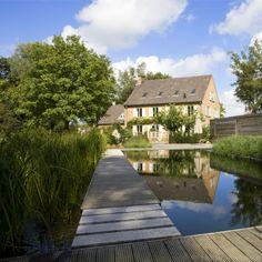 Zwemvijver in L-vorm in landelijke tuin met cederhouten poolhouse ‹ De Mooiste Zwembaden