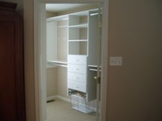 An example of a walk in closet with drawers and a pull out laundry basket.