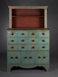 """n two parts with open shelves over a case of drawers. Reportedly from a doctor's office.  ~ ITEM DETAILS ~  Dimensions: Ht. 66 ¼"""", W. 43 ½"""", D. 18""""  Date / Circa: c. 1820-40  Maker / Origin: New Ipswich, NH  Medium: A 19th c. grain-painted finish was removed to reveal the original blue paint."""