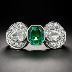 Giftwrap your finger in chic and stunning style. This truly gorgeous, early-Art Deco bow motif ring is knotted with a luscious, ultra-gemmy, old-mine Colombian emerald. The rich, deeply saturated, bright-green gemstone is bezel-set between a pair of sparkling, old mine pear-shape diamond-centered platinum bows. A truly splendid, far-from-ordinary, original Art Deco jewel in a finger size 6 3/4-7.