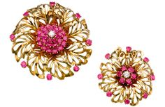 This pair of flower designed brooches/pendants was sold in Geneva in November 2011 by Christie's for 9,375 CHF. Set to the centre with circular-cut rubies and diamonds, these pieces can be used as pendants as well as brooches. This particular design is typical of John Rubel, who was one of the inventors of modular high-jewelry.