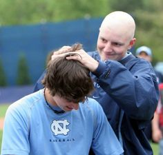 Chase Jones shaves the head of Tar Heel teammate Brian Moran during a Basebald fundraiser when they played baseball together at the University of North Carolina. Players shaved their heads in support of Jones, who received treatment for brain cancer.