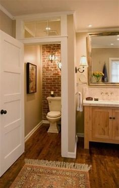 Toilet closet with wood floors, brick wall and glass panel at the top of the door.(I'm going to have a toilet closet,and I really like this). Style At Home, Toilet Closet, Home Interior, Interior Design, Bathroom Interior, Interior Ideas, Casa Clean, Beautiful Bathrooms, Small Bathrooms