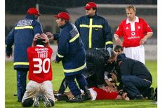 PLAYERS, RESCUE WORKERS AND MEDICS SURROUND BENFICA'S HUNGARIAN SOCCER STRIKER MIKLOS FEHER.