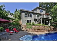 Great tiered landscaping & plenty of seating surround this in-ground heated pool | Des Peres MO