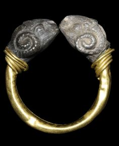 Ancient Macedonian hollow pen-annular finger ring with coiled wire collars; the silver terminals in the form of opposed rams' heads. 3rd century BCE.