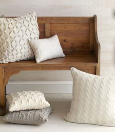 """Throw pillows take a smart turn wearing patterns normally found on preppy pullovers. Pillow covers (clockwise from top left): For similar, wool, $98; 18"""" square; chickspicksbyhillary.com. Cotton and canvas, $85; 12""""W x 16""""L; Simplemente Blanco, 617-734-3669. Alpaca, $175; 24"""" square; wildflowerorganics.com. Wool (bottom of stack), $69; 16"""" square; wool (top of stack), $79, 16"""" square; preciousknits.etsy.com. Pine bench, $1,099; 74""""W x 35 1/2""""H x 19""""D; arhaus.com."""