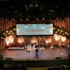 Tracy Grubbs from Lake Forest Church in Huntersville, NC brings us this repurposed design along with their cool design grid in the background. They got their inspiration from the design called Pallet Gaps by Santa Cruz Bible Church. Their building dudes cut all the pallets apart and since they were going after a more irregular look, they randomly assigned them a home and used a nail gun to attach the pallet pieces to the stage grid (see below for more on the grid). They sandwiched the…