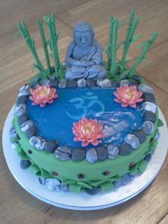 Fondant meditating buddha, om symbol in pond, and water lilies,...