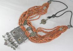 15 strands of fine graded coral beads with Ait Ouarzguit rare and ancient pendant made from a headdress piece originating in the rich saffron growing valley in the south of Morocco. Additional coin and plaques add that magical twist, the rare silver beads in this design are a delight in themselves! 80 cm clasp to clasp adjustable to 50 cm  pendant has a 10 cm drop weight 349 g please contact me for the price redsarah@live.com