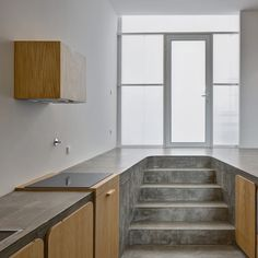 A concrete kitchen worktop doubles up as a dining room floor inside this renovated house in Porto.